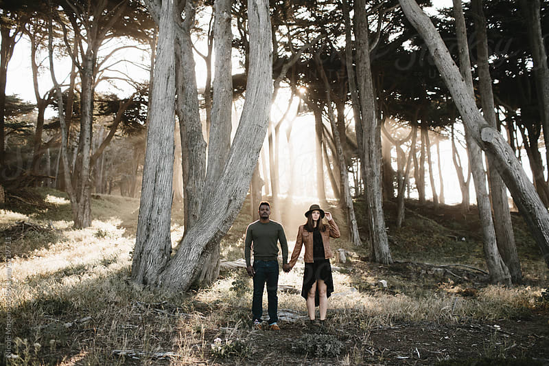 couple standing together in sunlit forest by Nicole Mason for Stocksy United