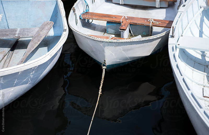 Trio of floating rowboats are tied to a dock by Cara Slifka for Stocksy United