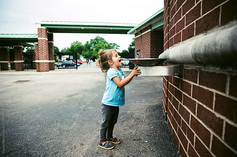 little girl tries to drink from water fountain by Maria Manco for Stocksy United