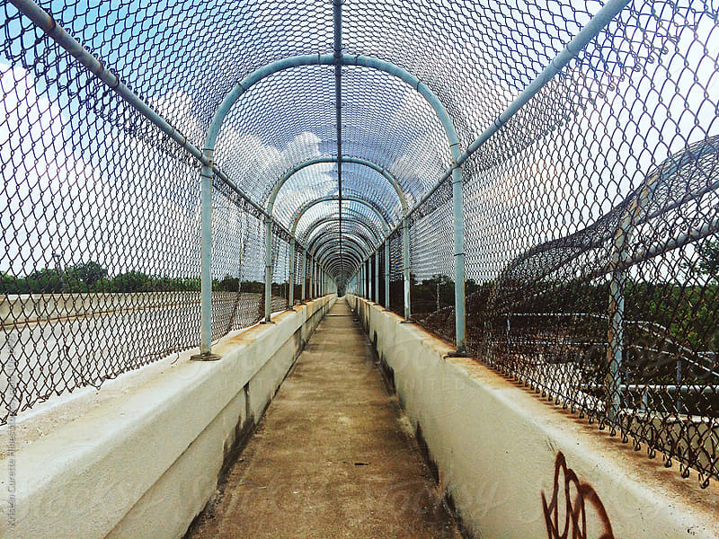 Mobile photograph of an old highway sidewalk / fenced off by Kristen Curette Hines for Stocksy United