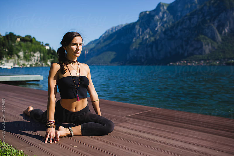 Woman doing Half Pigeon Pose  by michela ravasio for Stocksy United