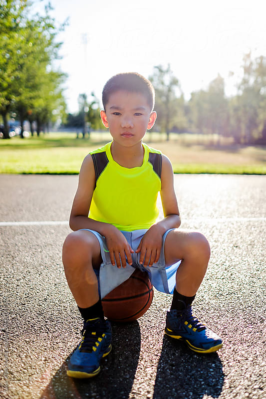 Asian kid sitting on a basketball in an outdoor basketball court by Suprijono Suharjoto for Stocksy United