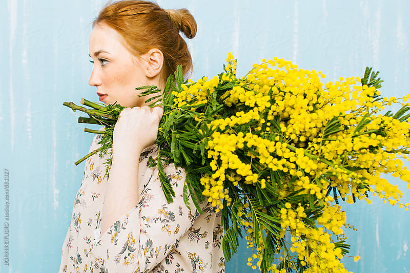 Side view of a ginger woman holding a big bouquet of yellow flowers. by BONNINSTUDIO for Stocksy United