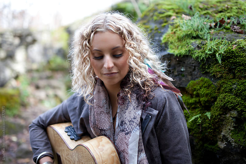 blond haired woman playing guitar in forest by Lisa MacIntosh for Stocksy United