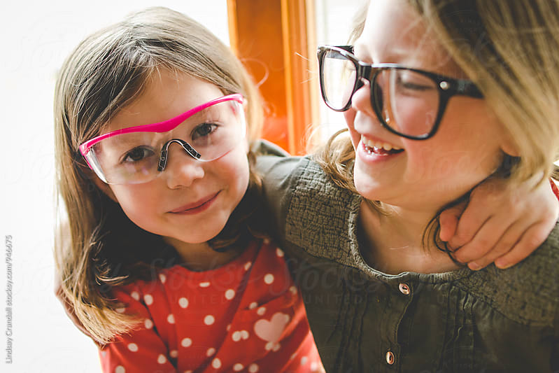Two happy young children wearing silly glasses and hugging by Lindsay Crandall for Stocksy United