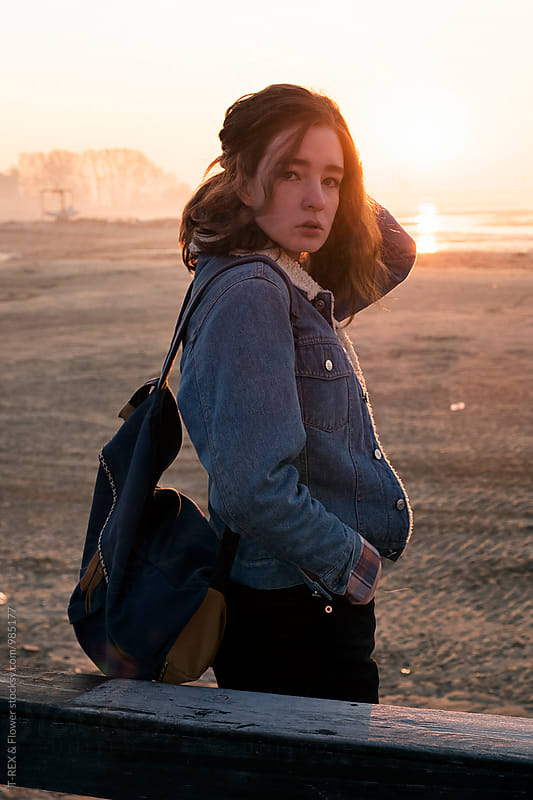Portrait of backpacker against of sunrise at beach by T-REX & Flower for Stocksy United