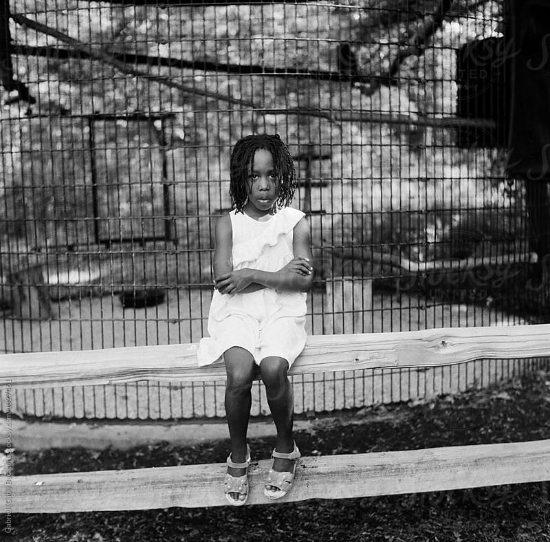 Black girl sitting on a fence by Gabriel (Gabi) Bucataru for Stocksy United