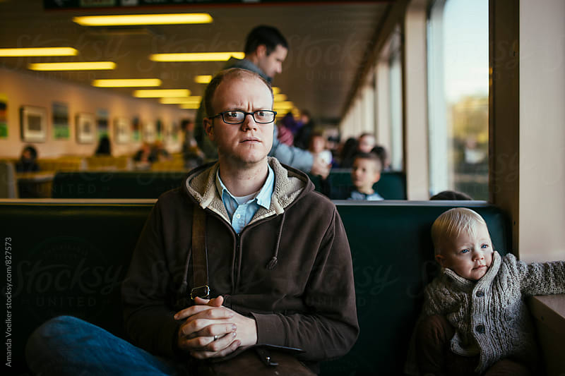 Father and Son Sit together on a ferry by Amanda Voelker for Stocksy United