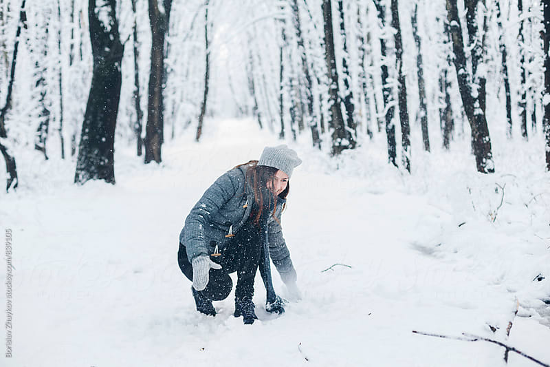 Caucasian woman playing in snow by Borislav Zhuykov for Stocksy United