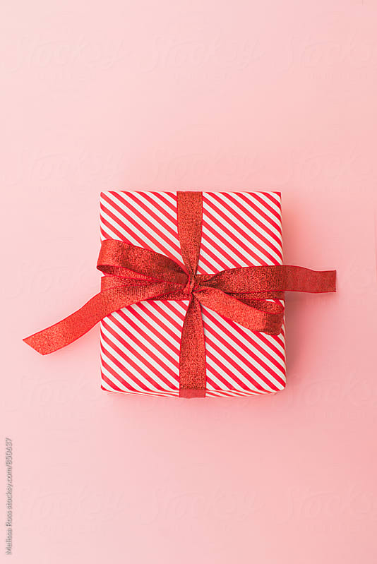 Small red and white wrapped gift on pink - tall by Melissa Ross for Stocksy United