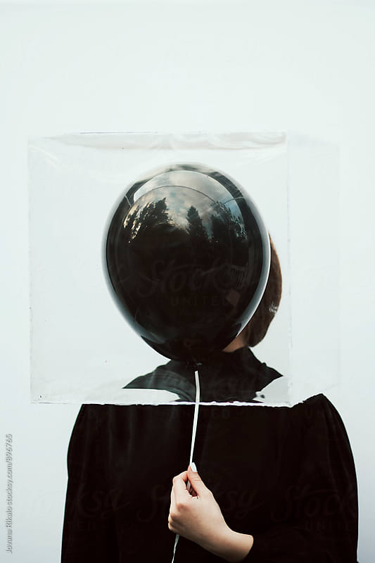 Artistic portrait of a young woman holding a black balloon by Jovana Rikalo for Stocksy United