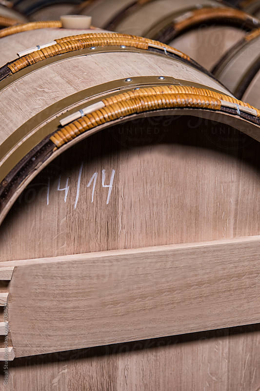 Wooden wine barrels stacked in a cellar by Bisual Studio for Stocksy United