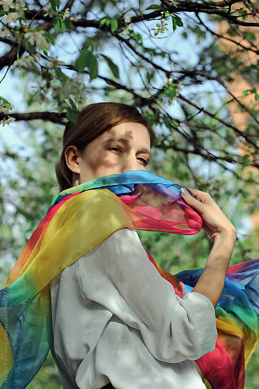 Girl playing with her colorful scarf under the tree by Hamza Kulenović for Stocksy United