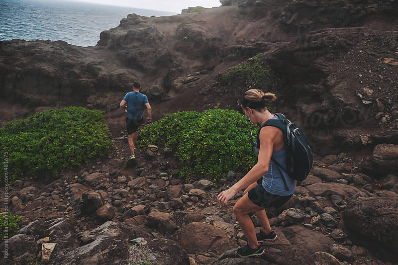 Young active couple hiking downhill in rocky landscape - hot climate by Rob and Julia Campbell for Stocksy United