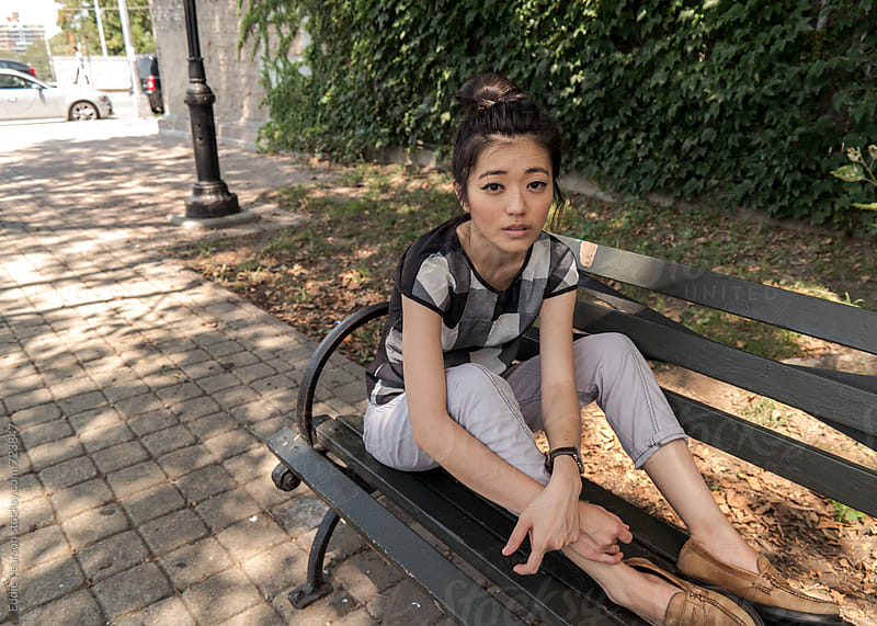 Beautiful young woman sitting on a bench by Eddie Pearson for Stocksy United