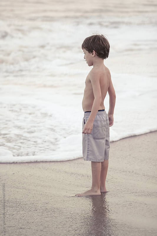 Young boy on sand by ocean edge by Kerry Murphy for Stocksy United