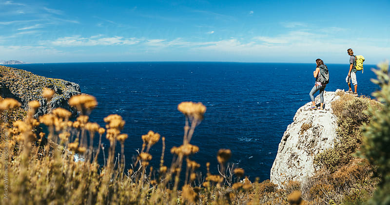 hikers on a rocky outcrop overlooking the sea in Greece by Micky Wiswedel for Stocksy United