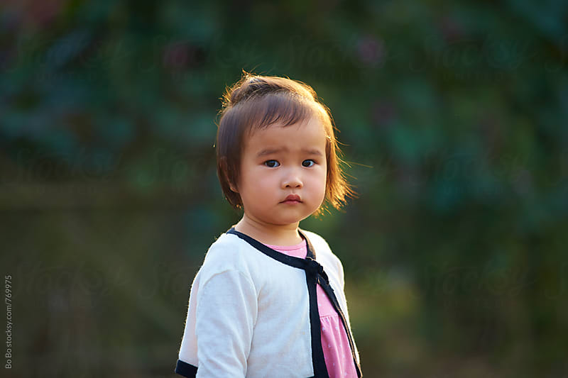 portrait of lovely little asian girl looking at camera by Bo Bo for Stocksy United