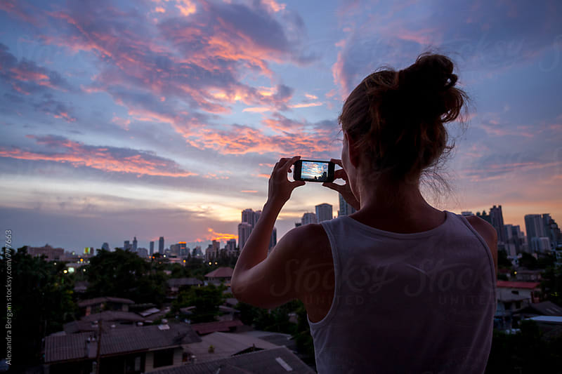Woman taking a picture of cityscape at sunset. by Aleksandra Kovac for Stocksy United