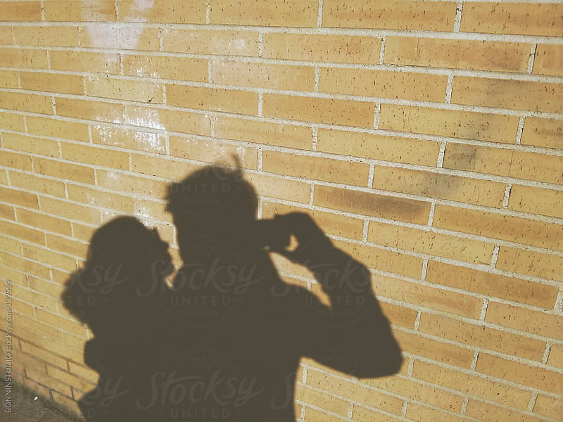 The shadow of a couple on a brick wall. by BONNINSTUDIO for Stocksy United