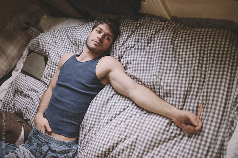 Man Resting in Bed at Home by Joselito Briones for Stocksy United