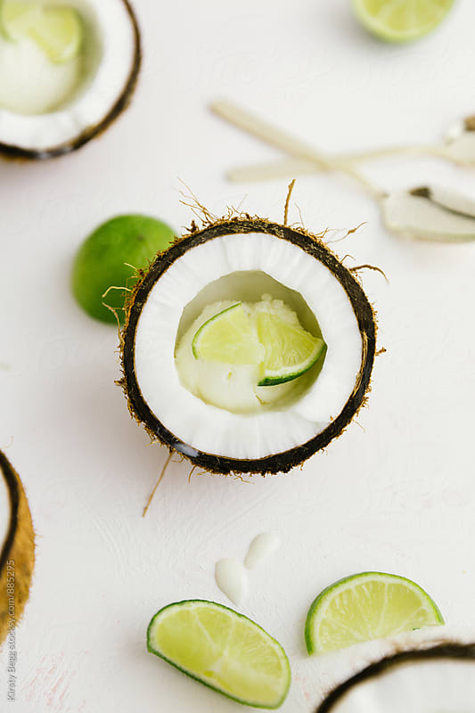 Overhead of coconut shell with lime wedges by Kirsty Begg for Stocksy United