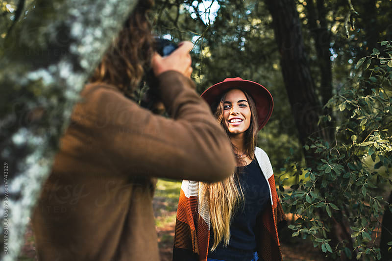 Man taking photos of his girlfriend in the woods. by BONNINSTUDIO for Stocksy United