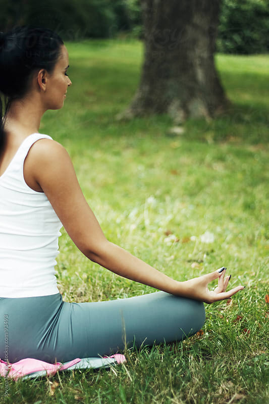 Young woman meditating in the park by Jovana Rikalo for Stocksy United