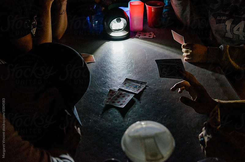 late-night card game at camp by Margaret Vincent for Stocksy United