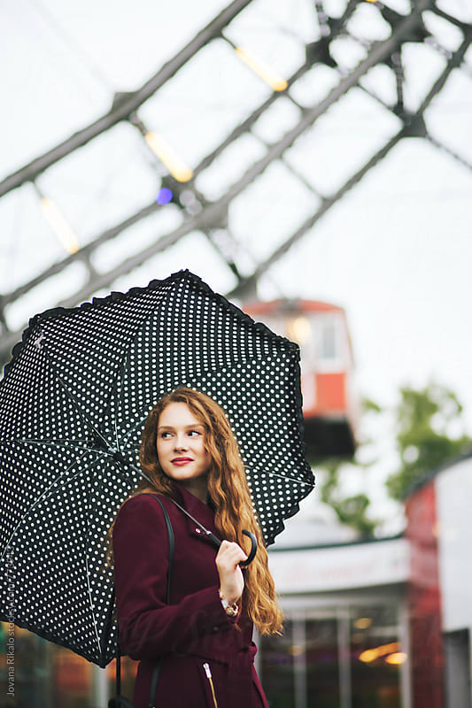 Beautiful ginger haired woman holding umbrella by Jovana Rikalo for Stocksy United