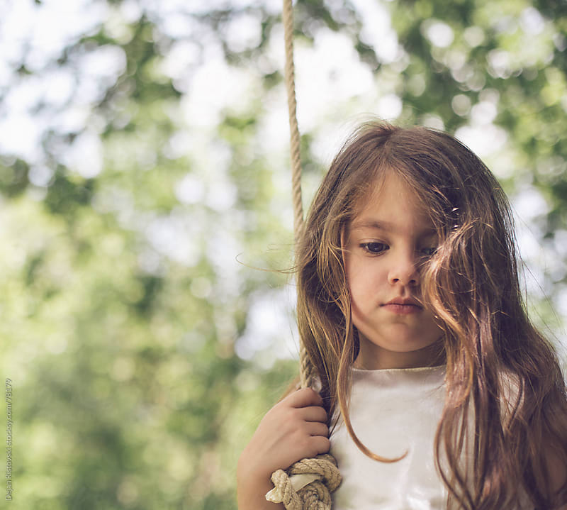 Little girl feeling sad in the park by Dejan Ristovski for Stocksy United