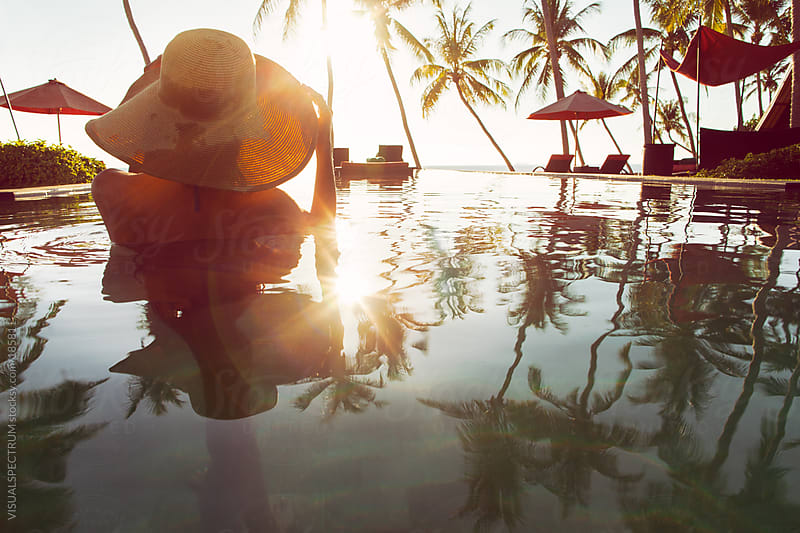 Woman With Hat Watching Sunset in Infinity Pool by VISUALSPECTRUM for Stocksy United