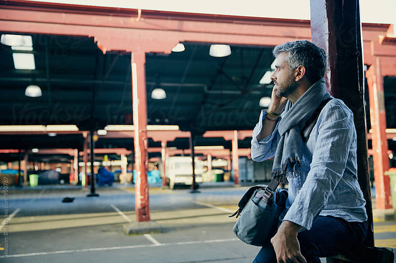 Grey haired man speaks on the phone in an empty marketplace by Joaquim Bel for Stocksy United
