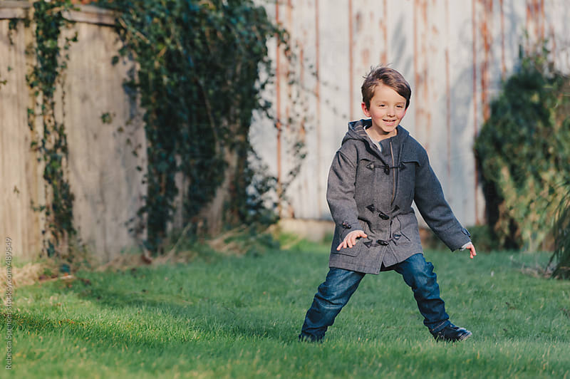 Child goalkeeping in backyard football by Rebecca Spencer for Stocksy United