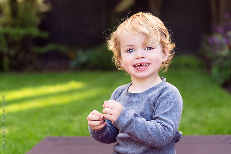 Portrait of a toddler in a yard in the evening by Angela Lumsden for Stocksy United