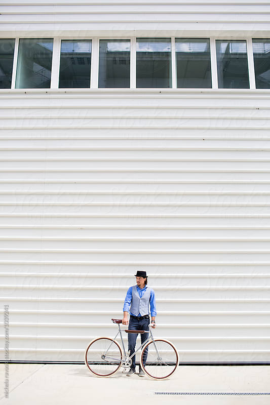 Handsome guy standing with his bicycle by michela ravasio for Stocksy United