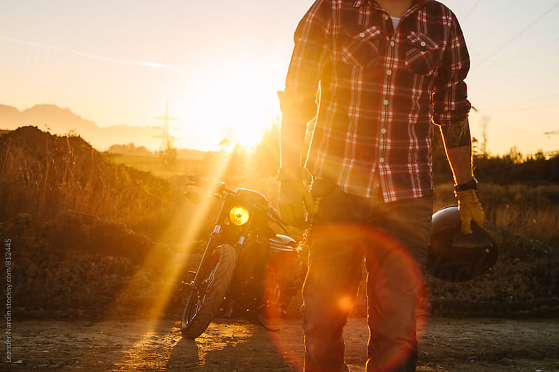 wild, young and free - deatail of a biker with helmet in his hand walking along a road at sunset with his bike in the back by Leander Nardin for Stocksy United