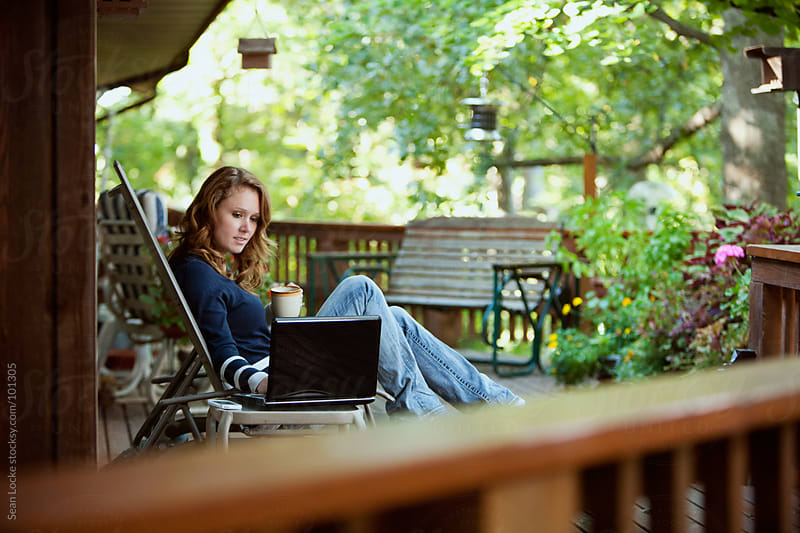 Working: Woman Relaxing While Checking Up On Business by Sean Locke for Stocksy United