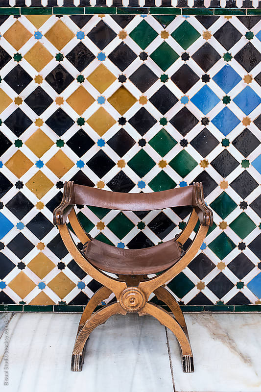 An old chair in front of colorful tiles by Bisual Studio for Stocksy United