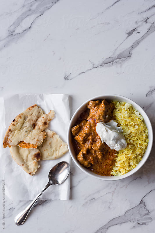 Indian curry in a bowl with cauliflower naan bread on the side by Gillian Vann for Stocksy United