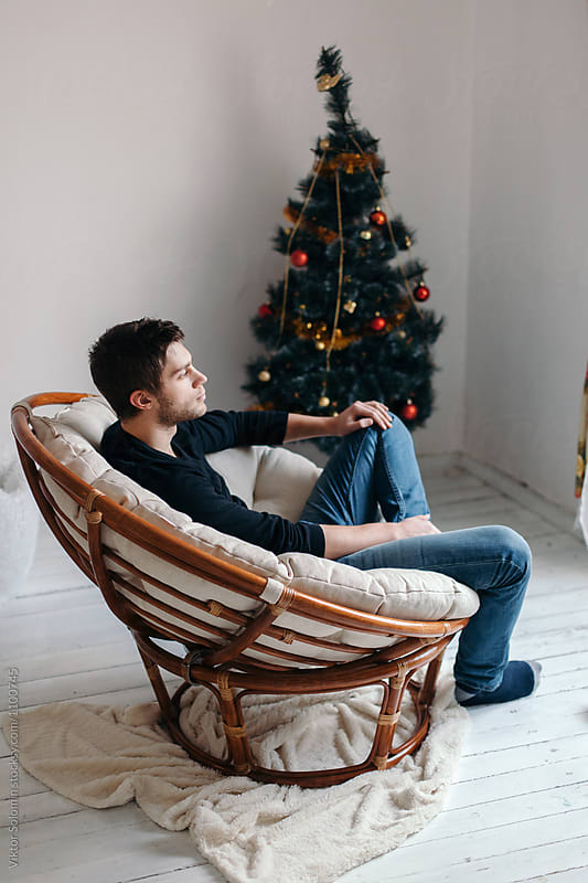 Young man sitting calm alone in armchair in christmas eve  by Viktor Solomin for Stocksy United