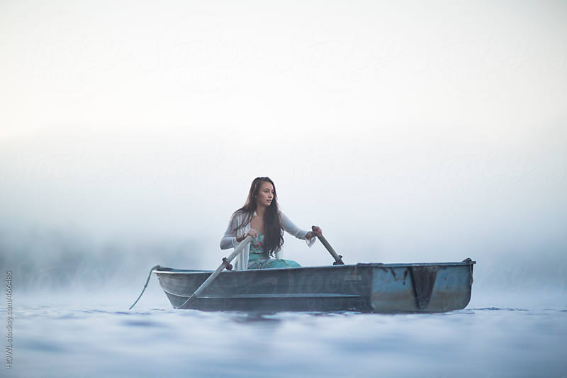 Beautiful woman in row boat on a foggy New England Morning by HOWL for Stocksy United