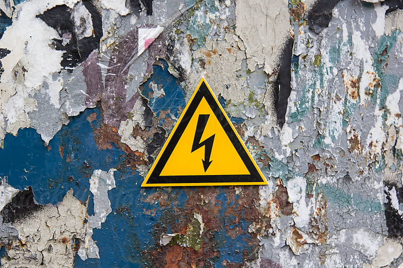 Electricity sign on a metal door covered with paint residue by Melanie Kintz for Stocksy United