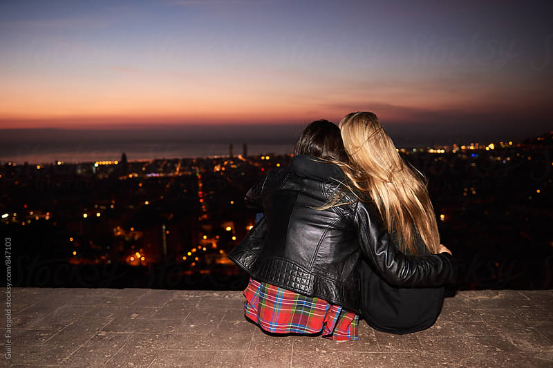 Back view of two girlfriends hugging while looking at evening cityscape by Guille Faingold for Stocksy United
