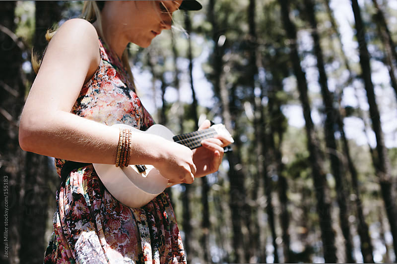 Girl standing in a forest playing a ukelele by Jacqui Miller for Stocksy United