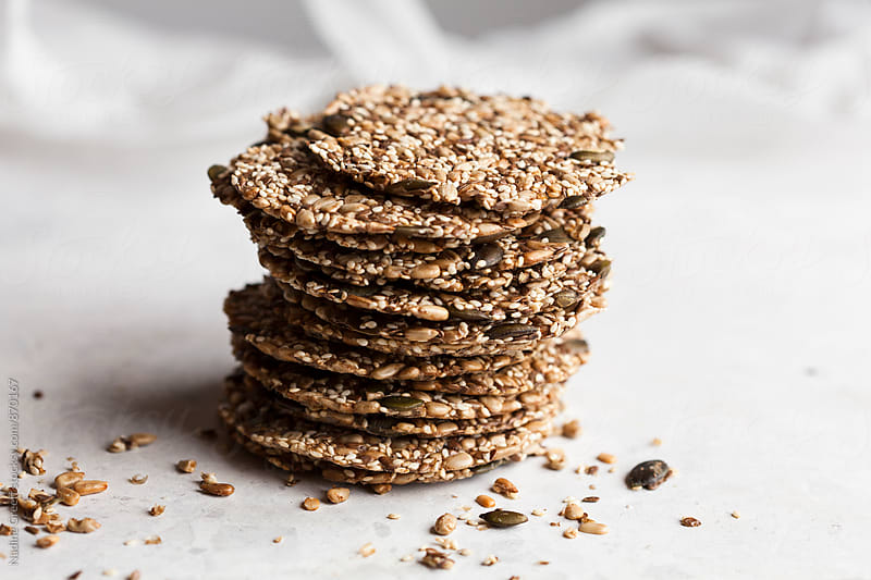 Healthy snack of seed crackers by Nadine Greeff for Stocksy United