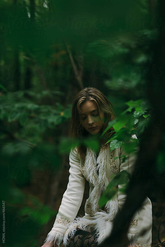 Blonde girl sits and waits patiently in a forest of green by HOWL for Stocksy United