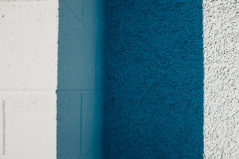 Corner of building wall exterior, painted different shades of blue and casting shadow by Paul Edmondson for Stocksy United