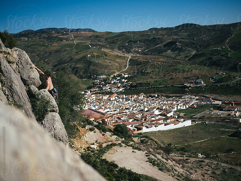 Wide shot of climber climbing above city in El chorro mountains by Martin Matej for Stocksy United