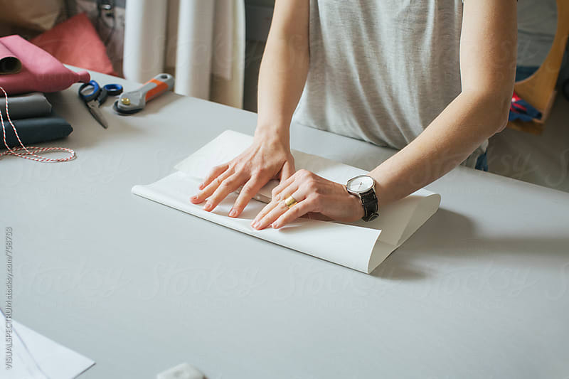 Close Up of Caucasian Woman Wrapping Homemade Product in Bright Dressmaking Atelier by VISUALSPECTRUM for Stocksy United
